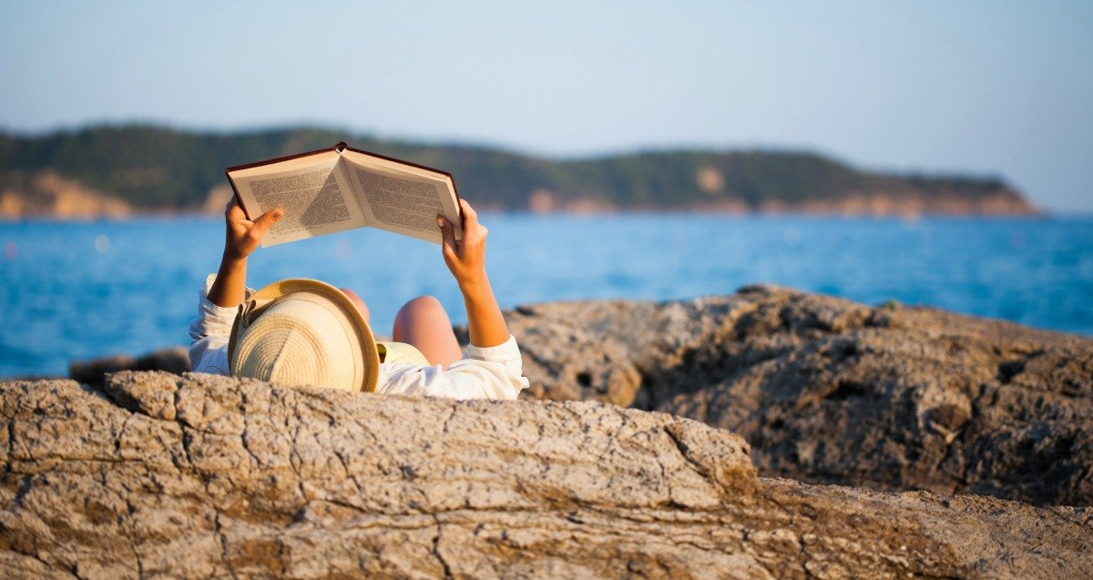 woman reading on the rocks