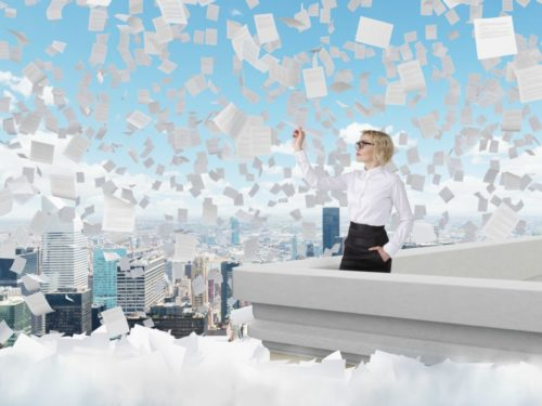 Businesswoman standing on roof throwing paper plane, Paris view, papers flying around. Blue sky at background. Concept of starting new project.